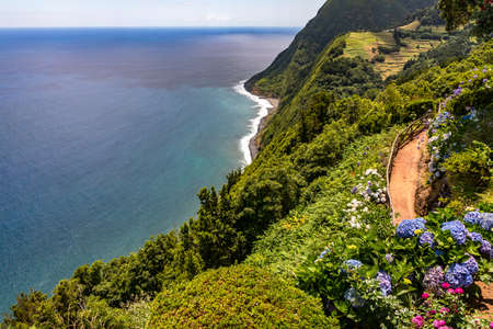 Lonely beautiful viewpoint overlooking the sea and the lush nature of the Azores