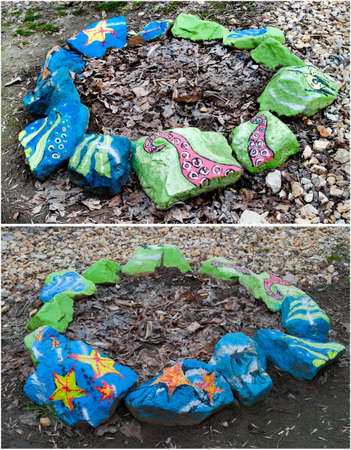 Flowerbeds of painted stones in green and blue with drawings on the marine theme photo