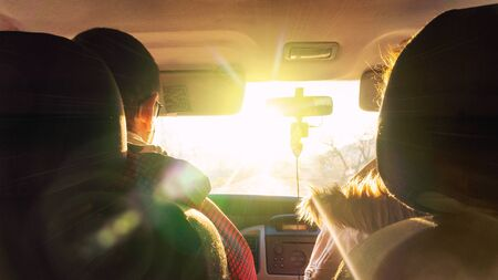 The man and the woman in the car rush towards to the dazzling sun