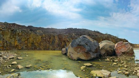 Prehistoric landscape. Large boulders of different colors lie in muddy water. A rocky cliff rises in the distance