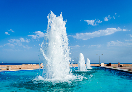 Diminishing Perspective of water fountains against a blue sky