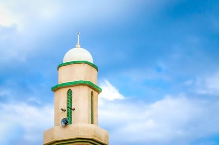 Majestic Minaret with Loudspeakers with Blue Sky in the background. Muscat, Oman.