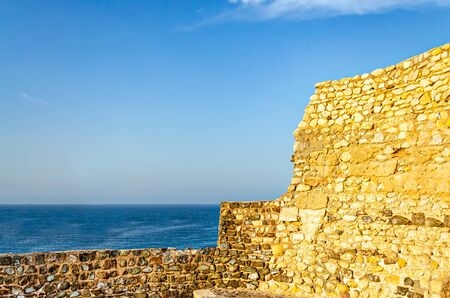 Old, abandoned and ruined fort wall opening to the blue sea with clear sky. From Muttrah, Muscat, Oman. 版權商用圖片 - 134862910