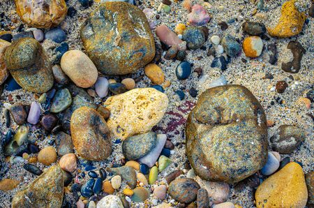 Smooth & Colorful pebbles buries in the sand on the beach. From Muscat, Oman.