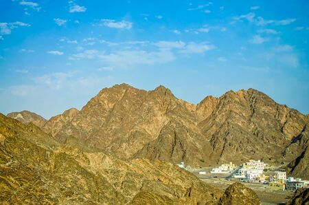 A small town surrounded by large pointy mountains on a clear sunny day. From Muscat, Oman. Stock Photo
