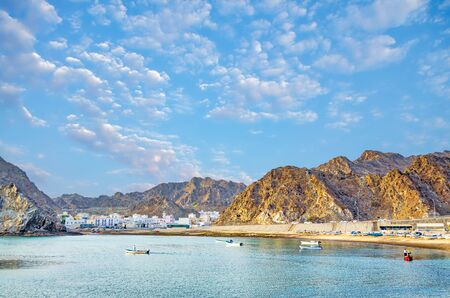 Fishing village between the mountains and the village folks fishing in the calm sea. From Muscat, Oman.
