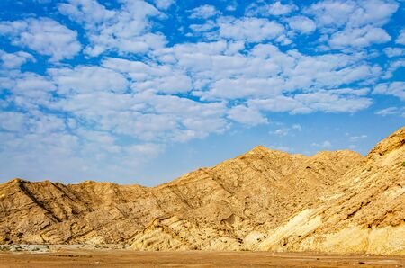 Orange Mountain range on a plateau with beautiful clouds as background. From Muscat, Oman.