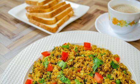 Egg Bhurji with coriander leaves and coconut along with bread and tea. Close up of a typical Indian breakfast.