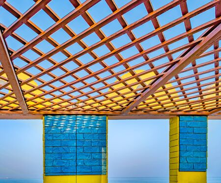 Yellow & blue beach shelter with open wooden panel on the roof facing a calm sea. From Muscat, Oman. Stock Photo