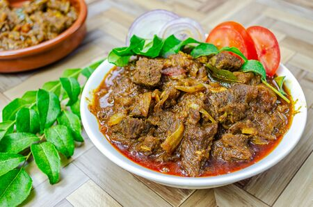 Traditional Kerala Beef Curry garnished with curry leaves, sliced onions and tomatoes Reklamní fotografie