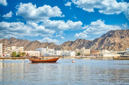Old Sailboat anchored at Muttrah Corniche. The the old city and mountains in the background. From Muscat, Oman. Stockfoto
