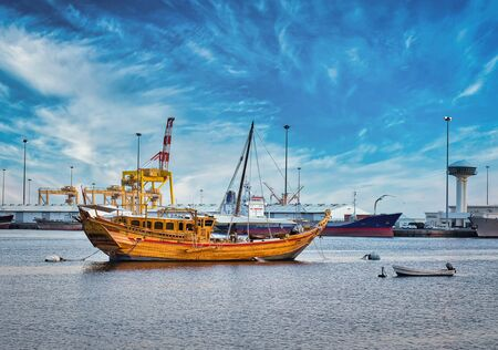 Traditional Omani Dhow anchored at the port along with the modern ships. From Muscat, Oman. Stock Photo