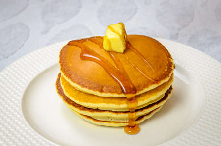 Read to eat sweet Pancake garnished with honey and butter in a round plate 免版税图像