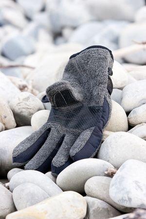 Abandoned glove on pebble beach Stock Photo