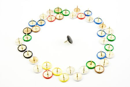 Brightly coloured drawing pins with concept of being surrounded and isolated Stock Photo