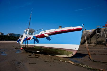 Colourful fishing boat sitting in sandy harbour scene