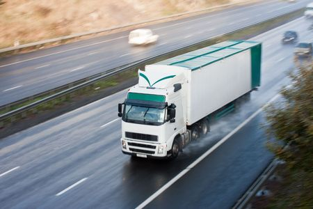 White and green truck blurred motion on wet motorway Stock Photo