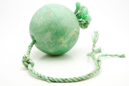 Well used green trawler net float with frayed coloured knotted rope