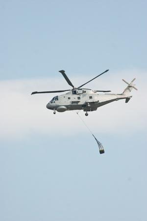 mago merlin: Helic�ptero de Merlin levantamiento de carga contra el cielo azul