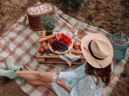 The woman in a straw hat has a summer picnic in nature with fruit and pink wine. Beautifully decorated picnic in Rustic style. Zdjęcie Seryjne