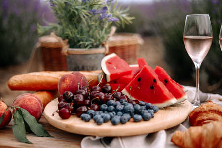 Fruits on a wooden tray and a glass of wine close-up. Picnic in nature in a lavender field.