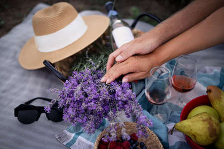 The man's hand holds a woman's hand. Summer picnic with fruit, wine and a bouquet of lavender.