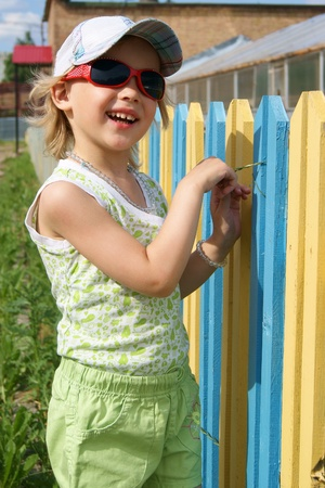 Smiling girl stands near a color fence photo