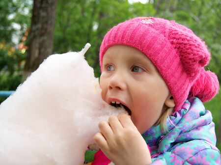 Little girl eats a cotton candy in the park Stock Photo