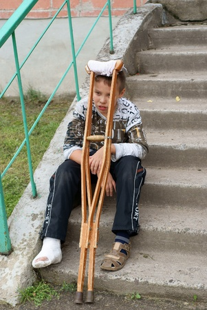 Boy with crutches sits on steps