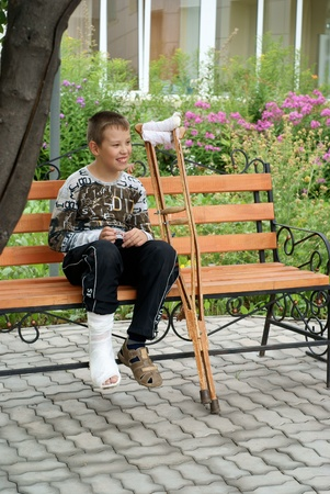broken house: Boy with crutches sits on a bench