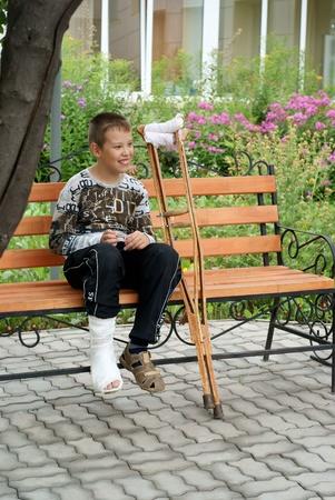 jambe cass�e: Gar�on avec des b�quilles est assis sur un banc Banque d'images