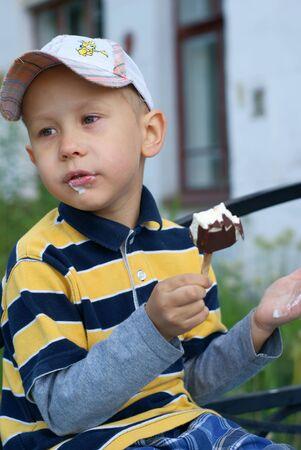 Boy eats an ice cream outdoor photo