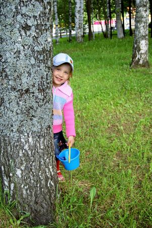 hides: Girl hides behind a tree Stock Photo