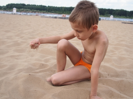 river trunk: Boy plays with sand at the beach