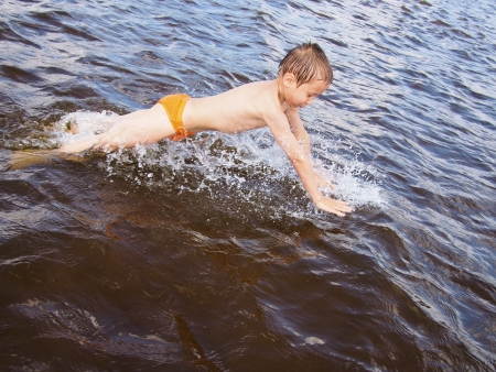 Boy jumps in water at the beach photo