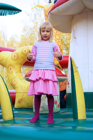 Little girl playing in color bouncy castle outdoor