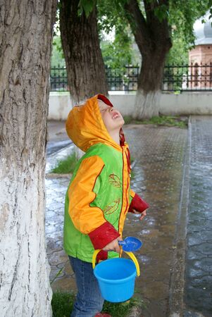 Little girl hides under a tree from the rain