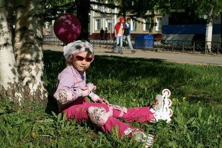 Little girl in roller blades sitting on the grass under tree Stock Photo