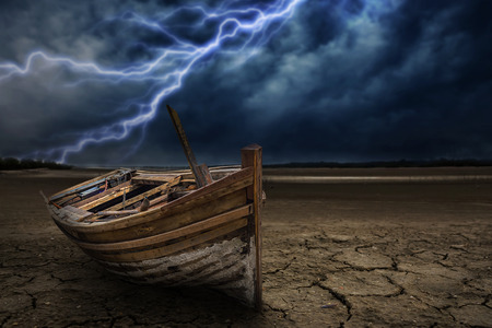 Boat crash land to the ground dry and cracked. With lightning storm Stock Photo