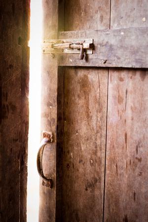 room door: Old dark room with shining closed door.