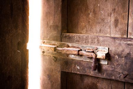 gulp: Old dark room with shining closed door.