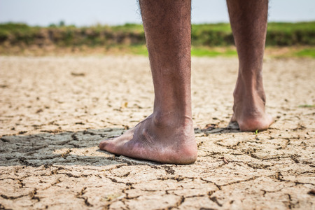 feet naked: Young man on dry soil Stock Photo
