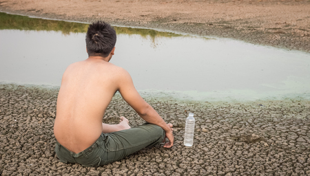 green house effect: Water crisis, man sit on cracked earth near drying water. Stock Photo