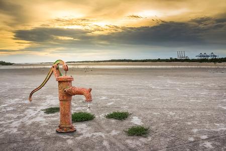 barren: Rusty water pump on barren ground sunset