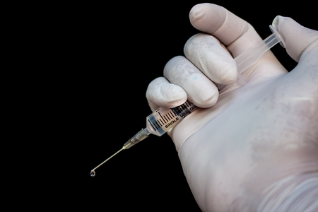 swine flu vaccine: Syringe in a hand in medical gloves, ready for injection with medication. Black background