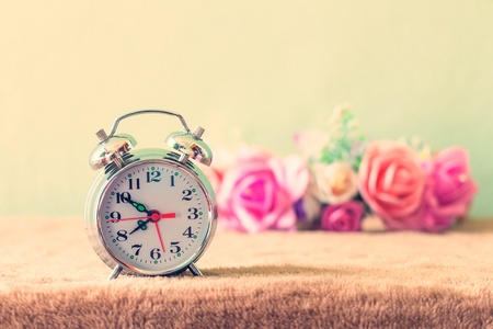 daylight: Small alarm clock with beautiful flowers on table vintage Style
