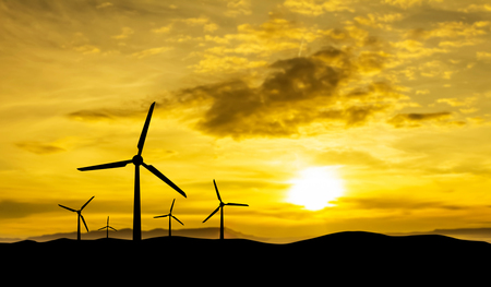 Alternative group of energy-producing windmills with sunset background.