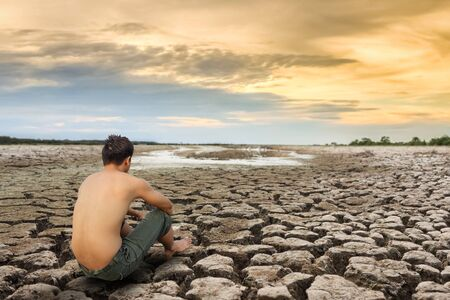 Water crisis, man sit on cracked earth near drying water. Stock Photo