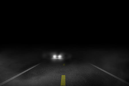 The lonely road fog at night with the car running.