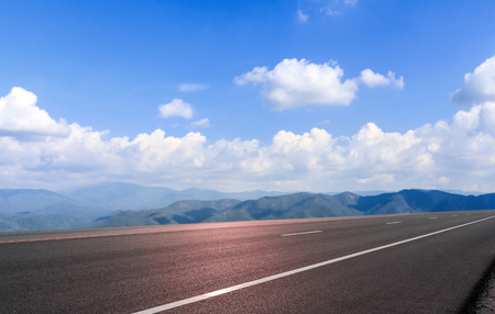 Road asphalt and mountain sky cloud background